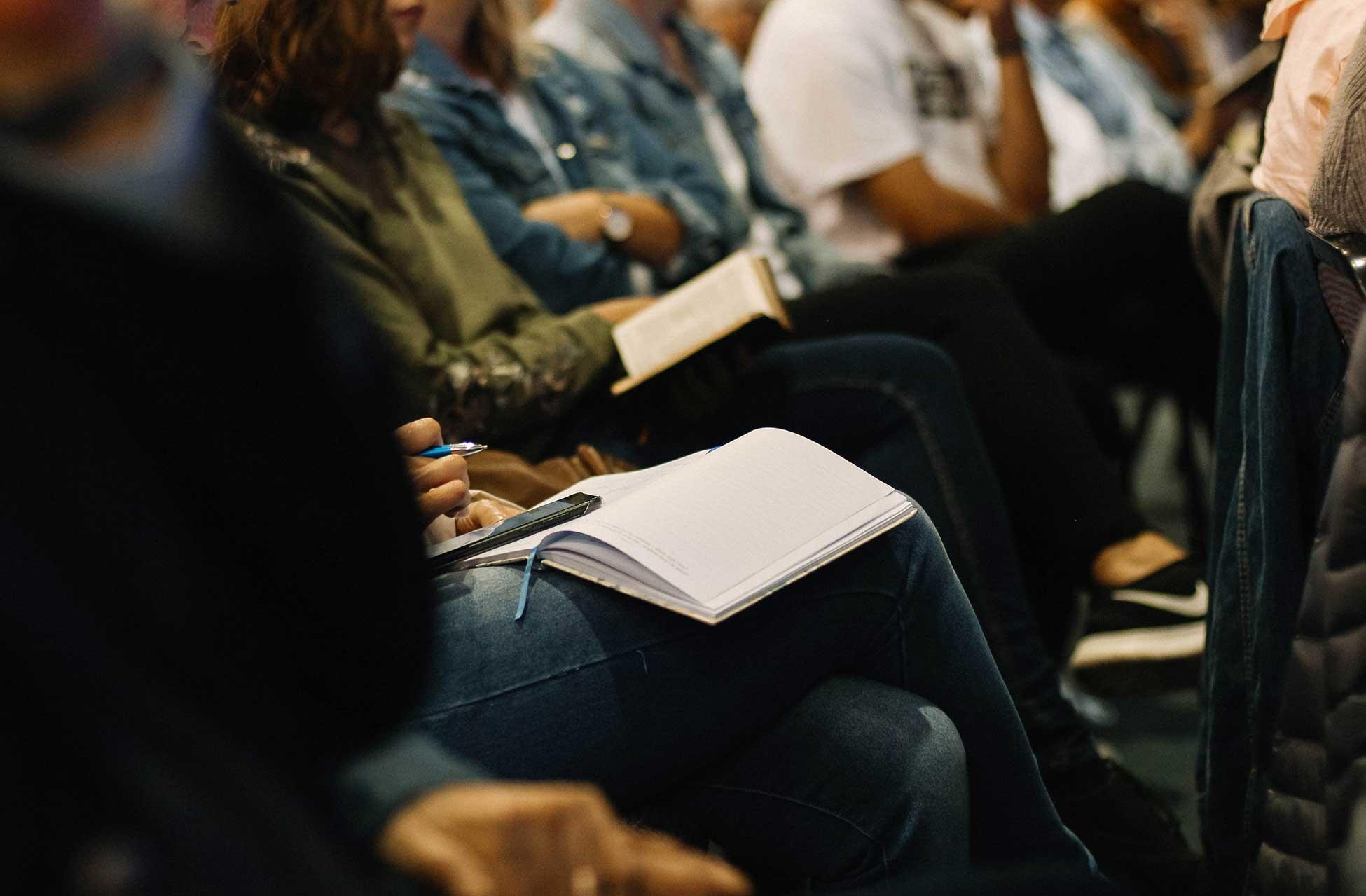 Menschen machen sich während einer Veranstaltung Notizen